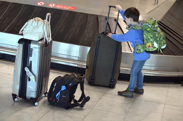 Leon mit ergobag am Kofferband des Flughafens